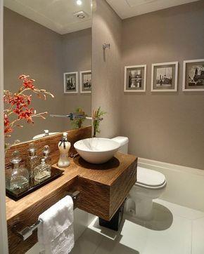 Esse lavabo mostra como escolhas corretas acrescentam luxo a um ambiente. Nesse caso, o rodapé alto, o cinza da parede em contraste com a bancada de madeira e as flores naturais.