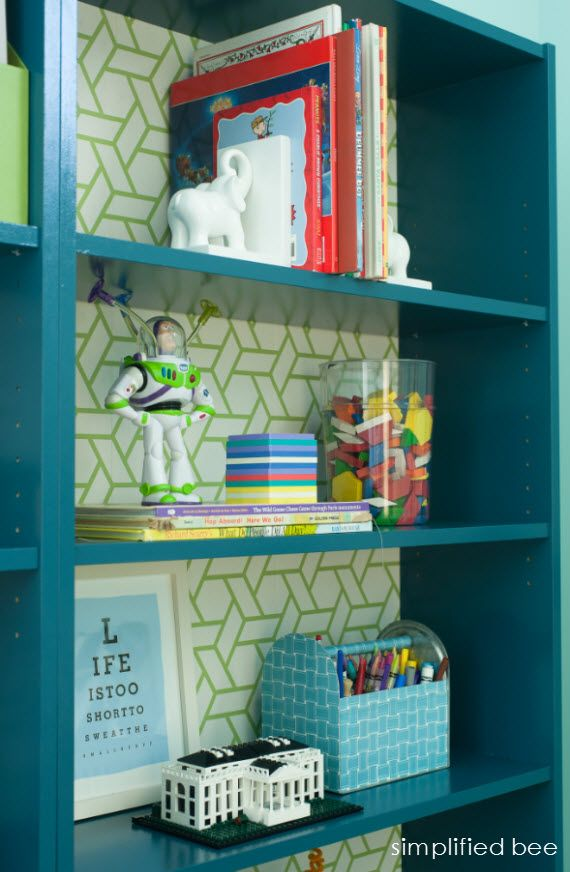 Painted BILLY bookcase with cool wallpaper backing via Simplified Bee