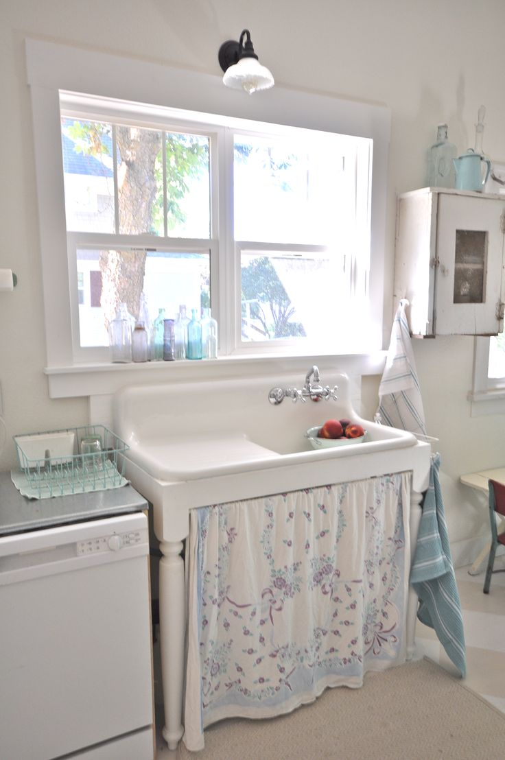 Vintage kitchen with farmhouse sink with vintage tablecloth skirt.
