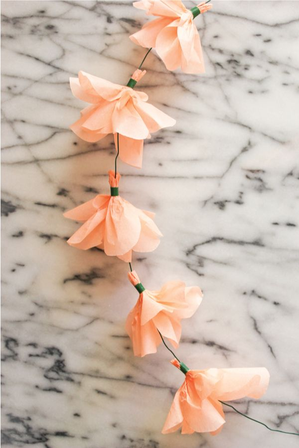 DIY~ Tissue paper flower garland. If this was done with white tissue pair dipped in purple it would almost look like that flower that brides hang in lines like this with a crystal at the end. Lol can't think of name! Place them closer together so don't see wire. Could work & be pretty & wow!.....so much less expensive!!!!