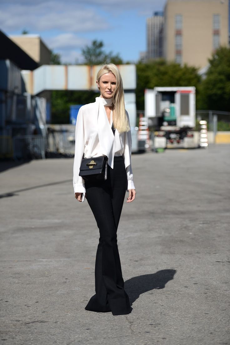 Celine Aagaard wearing flare pants and a chic white blouse during New York Fashion Week: