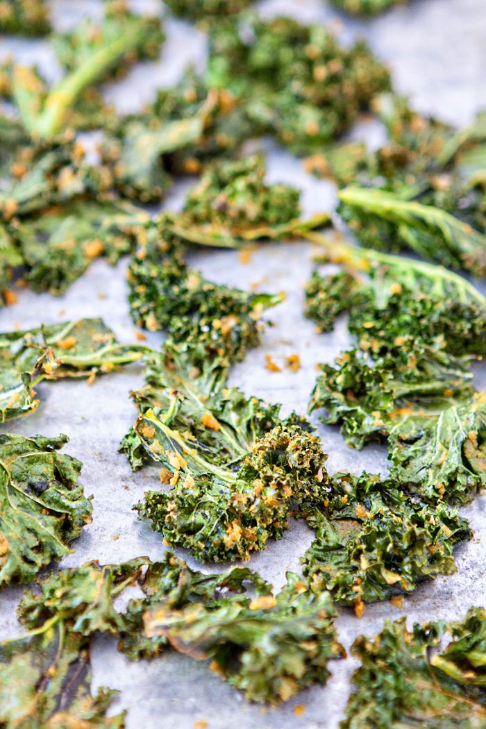 """These """"Cheesy"""" Kale Chips are a great, healthy way to satisfy your cravings for something salty and cheesy. Nutritional yeast gives them anutrient-rich cheesy flavor without any added dairy.  I find it a little funny that I'm writing a post about Kale Chips. Kale chips aren't a new thing by any means. I've successfully ignored and resisted them for a couple of years. IfI saw a post talking about how amazing they were or how Kale Chips are a great, healthy alternative when you're craving…"""