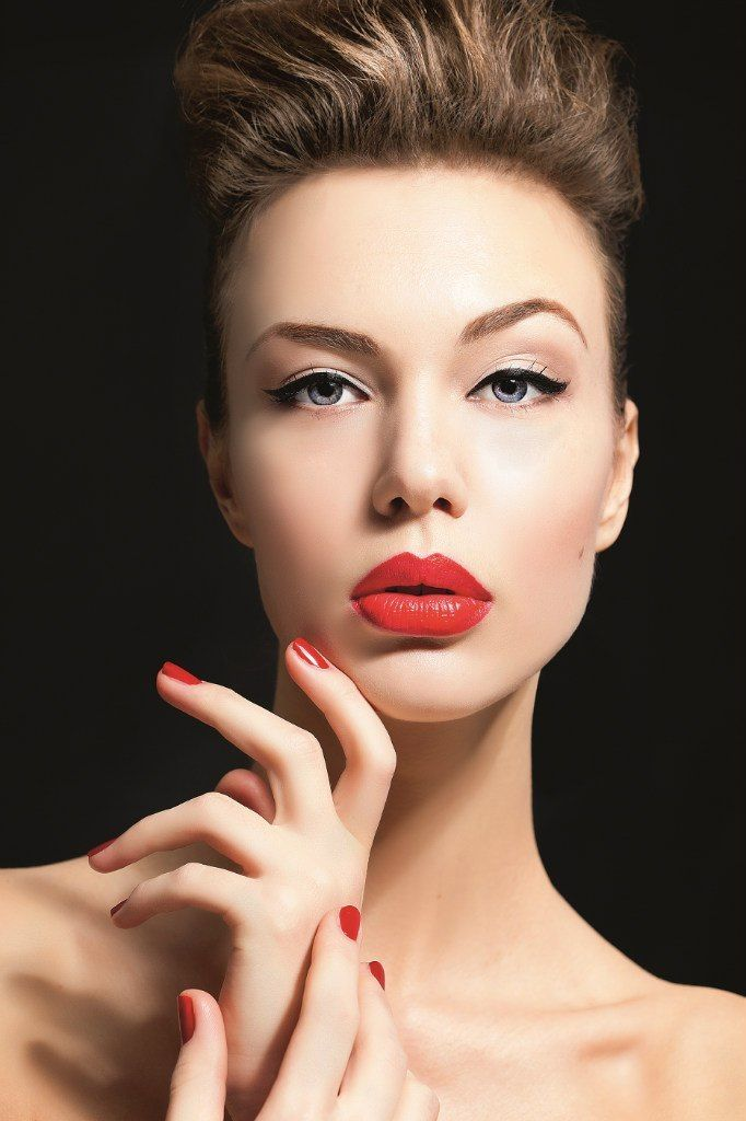 Classic red lip and black liner cat-eye. Pale-esque skin tone and light contouring.
