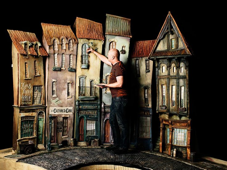Go Behind the (Crazy-Complex) Scenes of The Boxtrolls | Art director Curt Enderle and some of the buildings of Cheesebridge. (Note the many cheese puns in the film—like the stores Fun