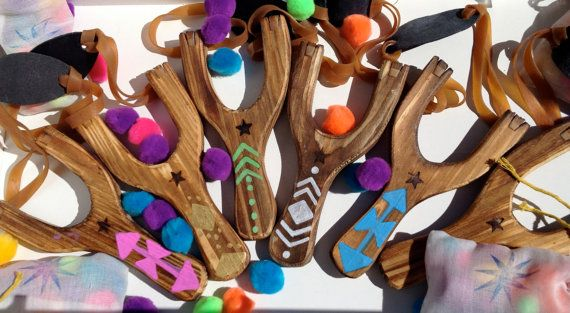 This 7 tall wooden slingshot has real rubber bands and a leather ammo pouch. Included is a muslin bag of cotton pom pom ammo suited for indoor use. Handpainted with a Native American inspired design, in the spirit of the Davy Crockett stories. Each slingshot is heat stamped with a star motif on the front. Please choose paint color for design on slingshot or no paint.  Makes for a great keepsake or decor, but with the sturdy construction, this is FULLY FUNCTIONAL, and should always be used…