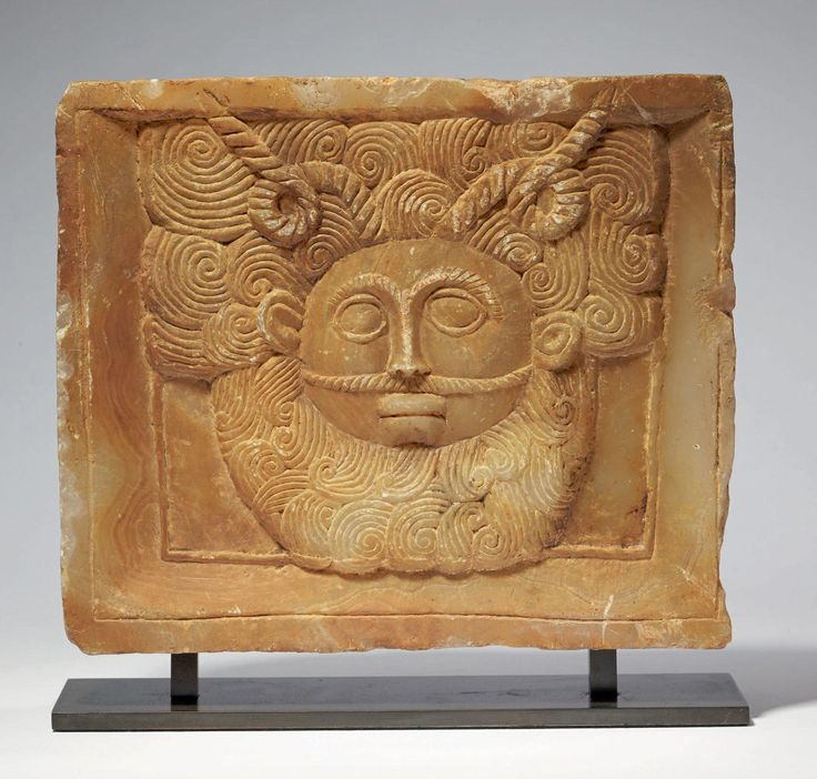 RARE PLATE VOTIVE sculpted face of a male deity face. The beard and hair are covered in long curly locks and the front sits atop two long spiral horns. Alabaster. South Arabian Peninsula, ca. First century BC. BC - I century AD .