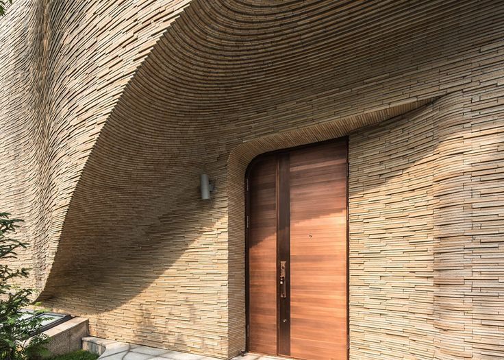 Small strips of clay-coloured stone create textured, undulating facades for the…