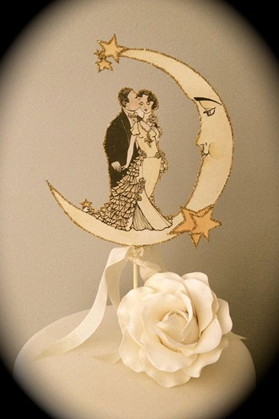 This vintage-inspired Art Deco cake topper is detailed in gold glass glitter.