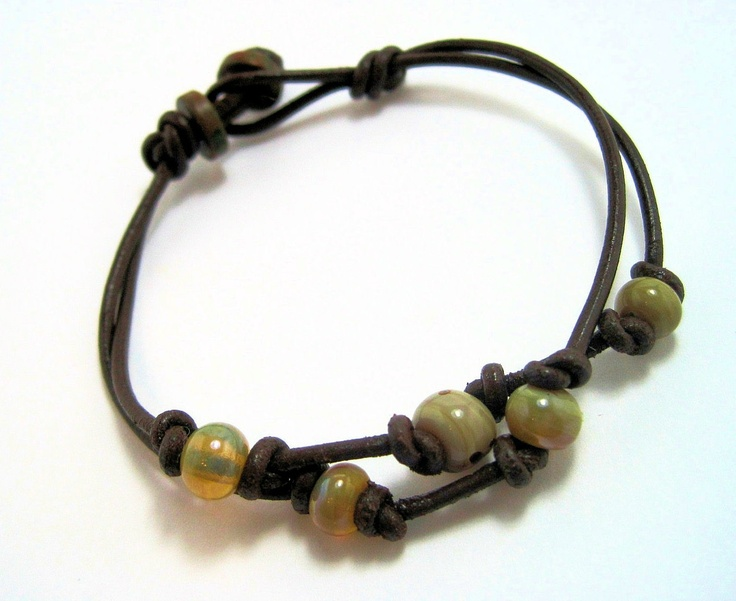 Used this as inspiration for two bracelets.  Will make another with two stands just like this one.  I see now that the length of leather is folded in half at the middle and then there is a looped knot - see the loop on the right.  Next add the beads to the two stands of leather and finish it with a button.