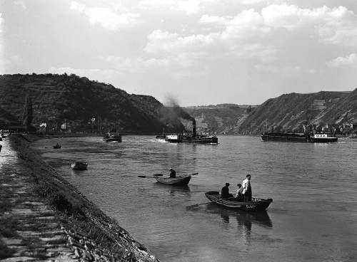 In einem Lotsenversetzboot wartet ein Lotse am Rheinufer von St. Goar auf ein Raddampfer, um diesen ungefährdet an Riffen, Klippen und Untiefen vorbei rheinaufwärts durch das Gebirge zu steuern. Ein Selbstfahrer fährt rheinabwärts.