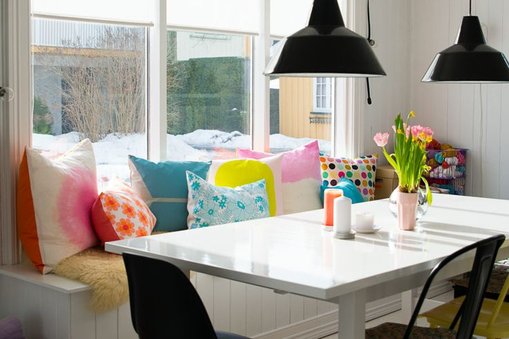 industrial black lighting, white table, mid century chairs, mixed seating, bench, bright, colorful pillows