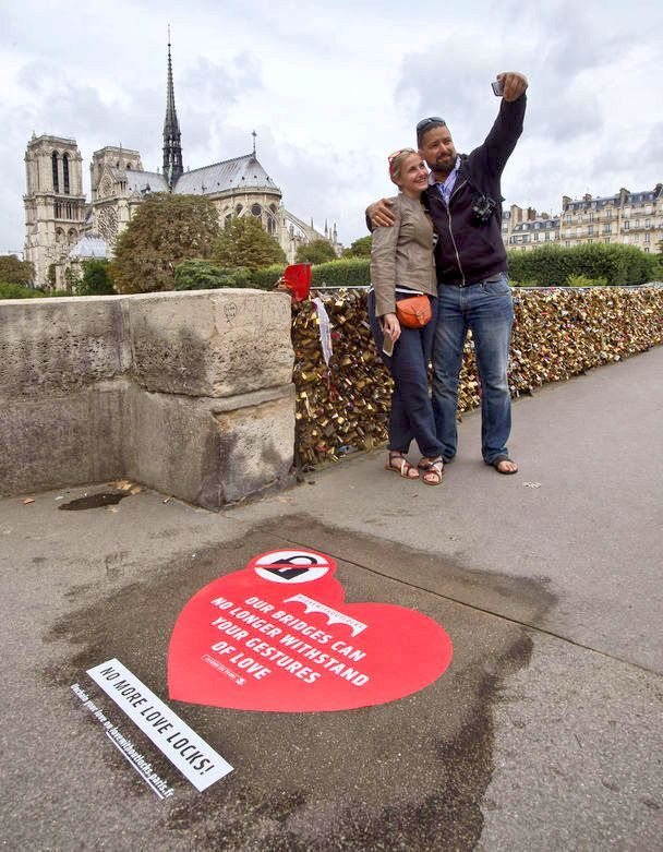 """FORGET THE LOVE LOCKS, URGES PARIS! • Paris hopes to persuade couples to end the unwelcome recent tradition of fixing padlocks to the Seine River's aging bridges, and instead upload hashtagged selfies to a website dedicated to enduring love. • Latvian honeymooner Regina and Vadim Medvedev pose for a selfie on a Paris bridge near a giant sticker against """"love locks."""" • :-) You think a selfie isn't a good replacement?"""