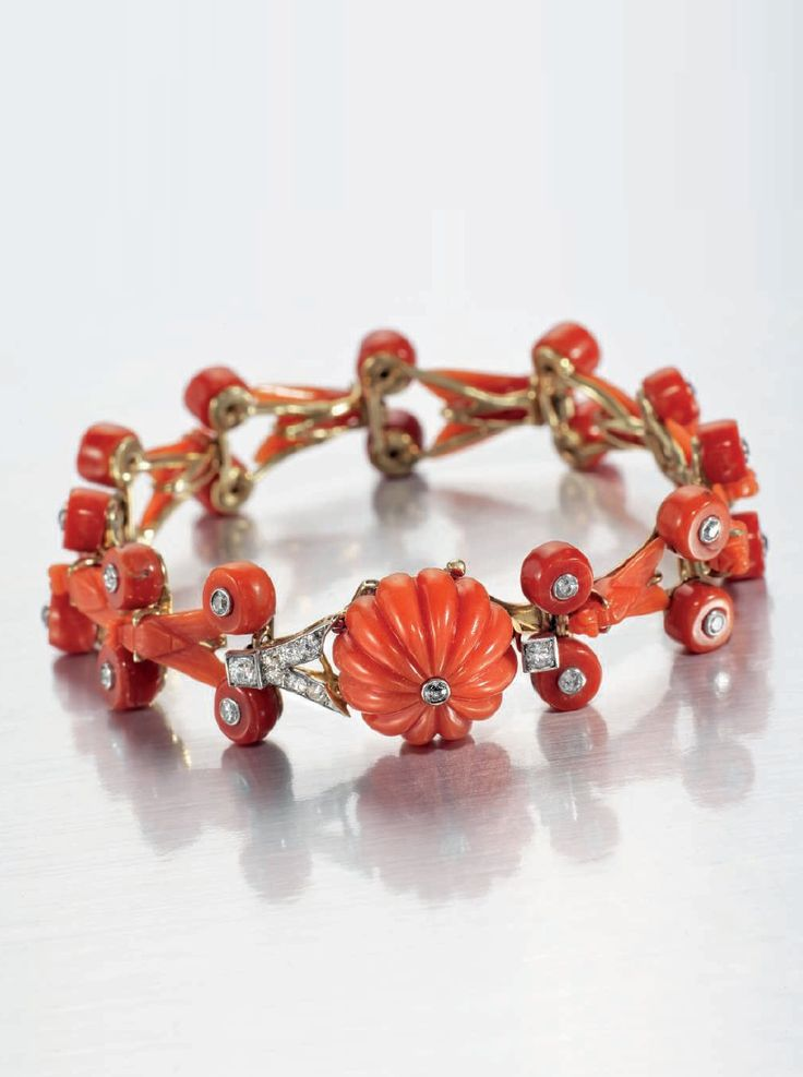 Cartier - An unusual Art Deco coral and diamond bracelet, circa 1925. Composed of a series of carved coral stylsed anceitn Egyptian flies with twin circular coral bead spacers, each bead with old-cut diamond collet accent, to a fluted coral bead clasp with central old-cut diamond collet and bufurcated side detail. Signed Cartier London, numbered.