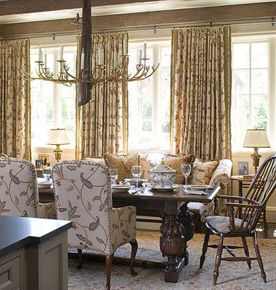 Plush draperies in a casual crewel fabric stretch from wall to wall in this English country breakfast room. The expansive window treatments give this space a cozy, intimate air.