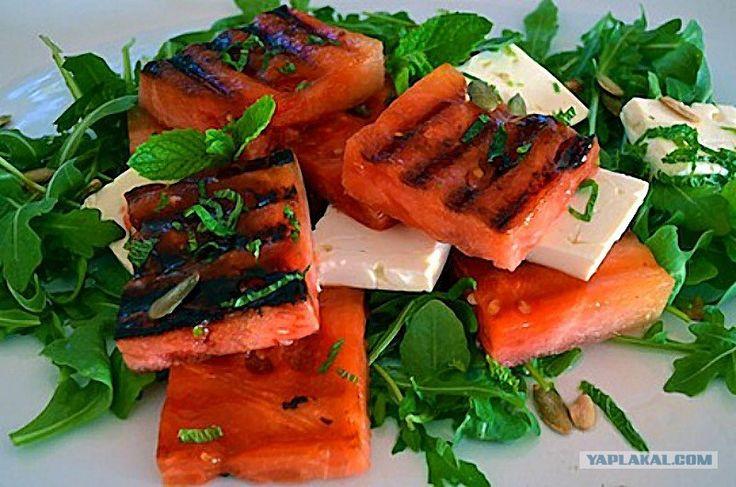 Для салата-закуски потребуется: 8 ломтиков арбуза без косточек (размером примерно с колоду карт); 2 столовые ложки оливкового масла; 5 чайных ложек сока лайма; 5 ломтиков сыра Фета (чуть более 100 грамм); горсть свежих листьев мяты; 3 чашки зелени (руккола, латук, кресс-салат); соль, перец — по вкусу; жареные семена тыквы.  Раскалите гриль. Просушите бумажным полотенцем кусочки арбуза и положите их на гриль. Обжаривайте с одной стороны, не переворачивая, в течение 2 минут. Перемешайте зелень…