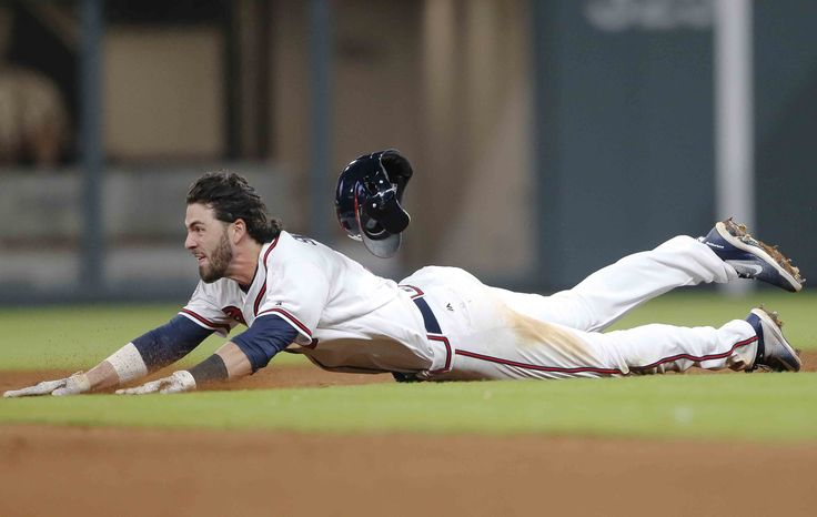 Atlanta Braves' Dansby Swanson dives into second base with a double in the ninth inning of the team's baseball game against the New York Mets Friday, June 9, 2017, in Atlanta. Swanson scored the winning run later in the inning to give Atlanta a 3-2 victory.
