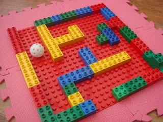 Pourquoi ne pas faire un labyrinthe avec des bloc de construction ?  Une balle légère et on souffle dessus pour la guider dans le droit chemin !