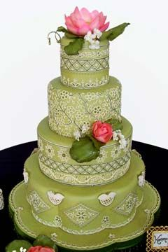 Round shaped, four tier green Indian wedding cake design, decorated with white intricate sari embroidery decorations and a large pink Lotus flower. from Sugar Creations.  love it.