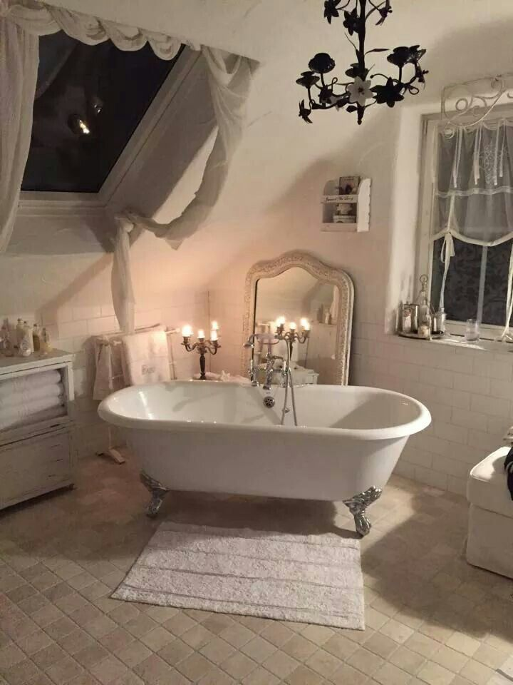 Romantic, shabby chic bathroom with a country look. Roll top bath, beautiful taps and mirror leaning against the wall. The candles add a romantic element. If you like this pin, why not head on over to get similar inspiration and join our FREE home design resource library at www.FlorenceAndFreya.com?