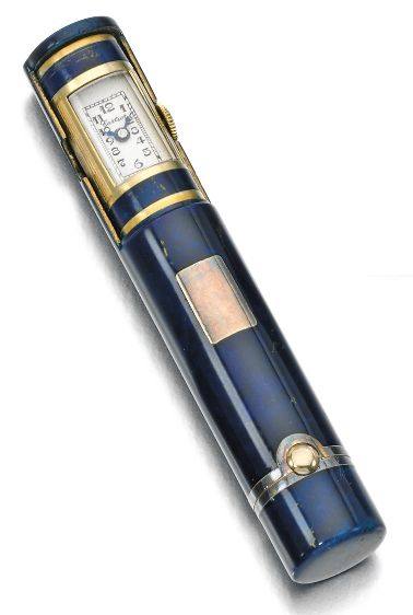 An Art Deco lLipstick holder/watch, Cartier, circa 1930. Applied with blue enamel, one end designed as a rotating drum concealing a watch, the rectangular dial applied with Arabic numerals, dial signed Cartier, numbered.