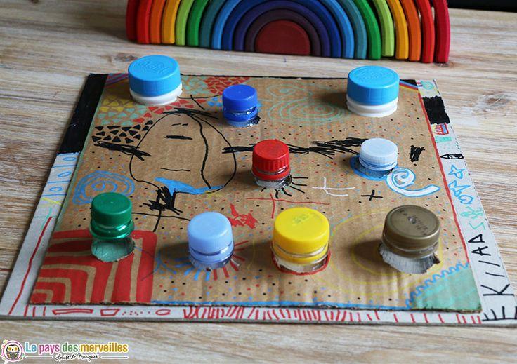 Cette planche à visser et dévisser Montessori est entièrement réalisée avec du matériel de récup' : bouteilles en plastique et cartons.