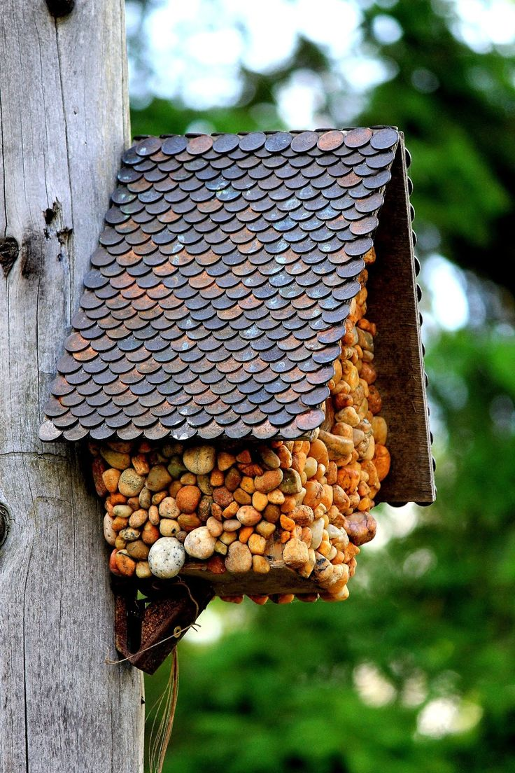DIY birdhouse featuring pebbles and a roof made of pennies