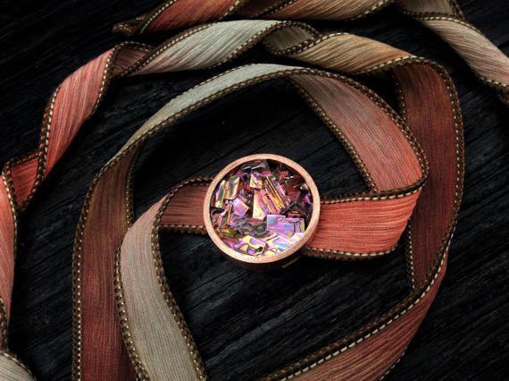 Il n'y a que deux éléments dans cette lunette magnifique bracelet: élément 83 (bismuth) et élément 29 (cuivre). Le ruban de soie belle, teint à la main peut être utilisé comme une enveloppe pour votre poignet ou votre cou et accents magnifiquement le flash fantastique de couleurs à partir du cristal de bismuth.  Diamètre du cristal est de 1 pouce, et le ruban est en 100 % soie asiatique et environ 42 de long. Les rubans sont cousus à un point à chaque extrémité. La main soie teinte est très…