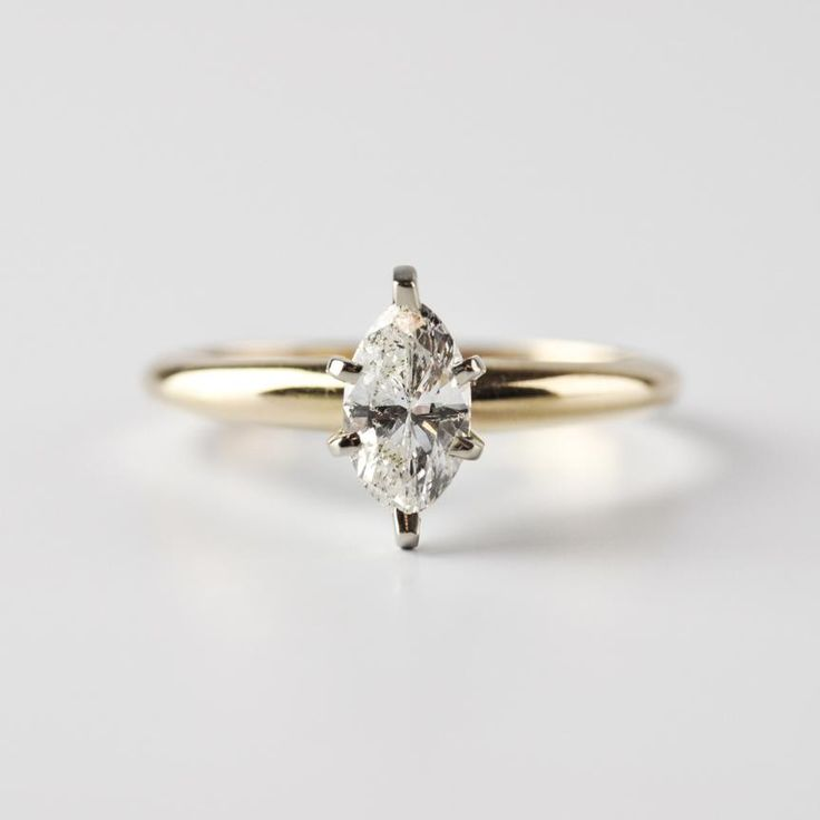 This Beautiful 14K Yellow Gold Engagement Ring Features A 0.50 Carat, Marquise Cut Diamond Set In 14K White Gold. The Diamond Is H In Color, And Has An 12 Clarity.