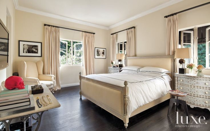 In a guest bedroom, Stanley designed an upholstered bed and dressed it with linens from Matteo. A pair of skull lamps from Blackman Cruz creates an appropriate counterpoint to the intricate lines of the inlaid matching chests.