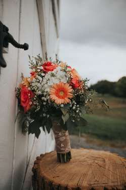 A Rustic Country Farm Wedding | Kaylon + John info@warrenwoodmanor.com Country rustic bridal bouquet of baby's breath, coral roses and coral gerber daisies with burlap wrap