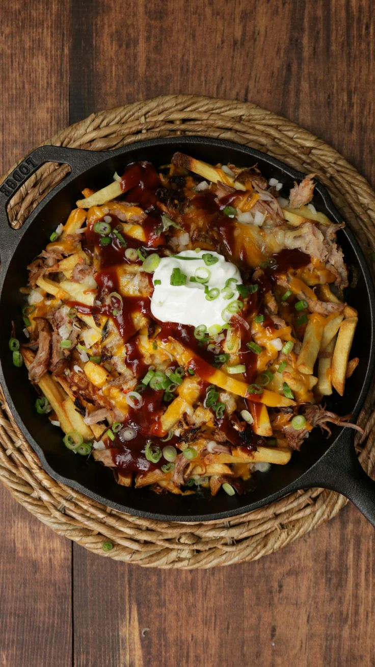 Recipe with video instructions: How to make BBQ pulled pork fries.  Ingredients: 2–3 lbs pork shoulder, Salt and pepper, 1 cup root beer, 2 cups barbecue sauce, Large bag of frozen french fries, ⅓ cup white onion, minced, 1 cup shredded pepper jack cheese, 1 cup shredded cheddar cheese, Chopped scallions, sour cream, extra barbecue sauce for garnish