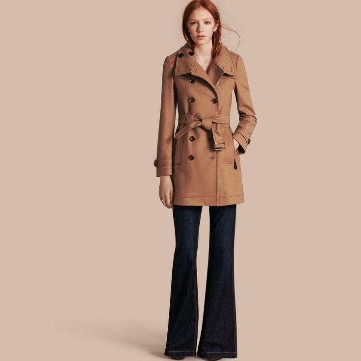 A modern interpretation of the iconic trench coat crafted in a double wool blend twill. Metal buttons and leather zip pulls complement the heritage-inspired design, while the funnel collar provides protection from the elements.