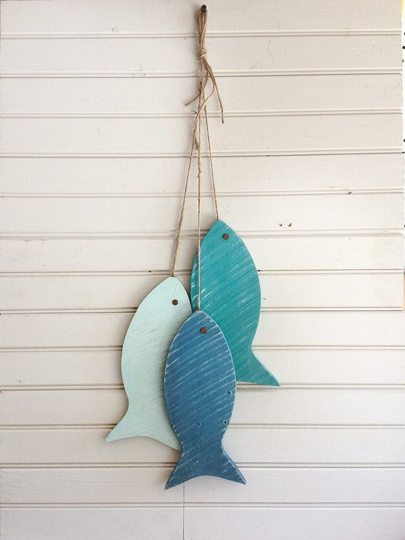 This whimsical painted fish decor is a set of three colors made from discarded pallet wood. They simulate a great days catch, hanging with jute