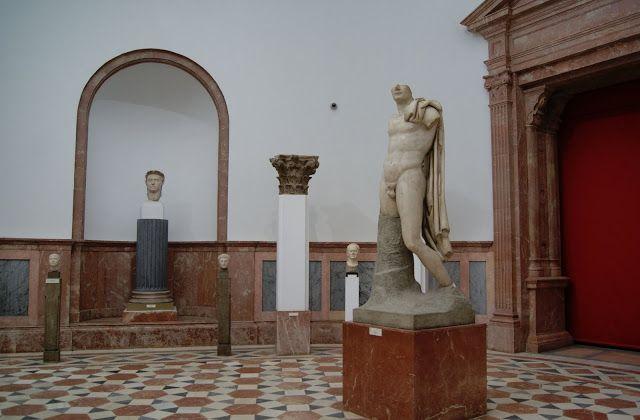 representación heroica del emperador Trajano, el cual aparece desnudo y con un manto sobre el hombro izquierdo, cayendo en pliegues rectos por el mismo lado en la espalda. Adopta la actitud del general en jefe (imperator) en acto de arenga. Debió llevar el cetro en su mano derecha, levantada, y tal vez una espada en la izquierda. La estatua fue descubierta en Itálica en 1788, habiendo sido erigida en tiempos del emperador Adriano.
