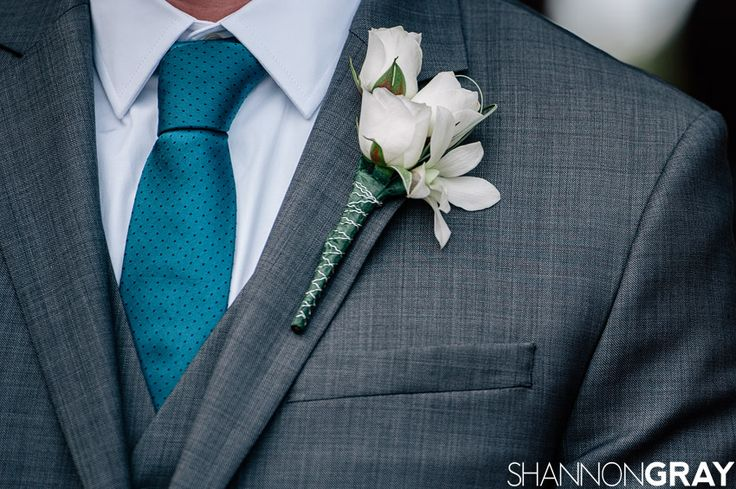 Gray suit, teal tie, white flowers