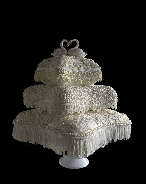 White fondant pearls lace pillow wedding cake with white sugar swans cake toppers.