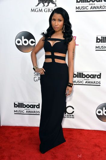 Presenter Nicki Minaj channels sultry glamour with a fun cutout twist in her floor-length black Alexander McQueen gown.