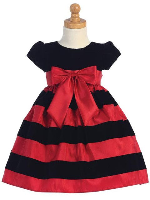 This holiday dress features a striped skirt of black velvet and flocked red taffeta. The top has a black velvet bodice with short cap sleeves, a rounded neckline and zippered back. Gathered waist with