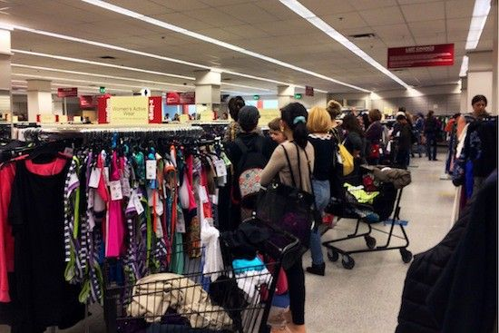 Shoppers clear the area while employees re-stock racks.