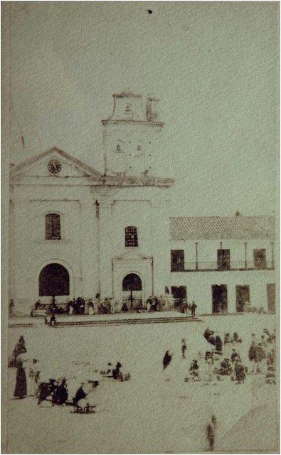 Plaza Mayor (hoy Parque de Berrío) y la Iglesia de Nuestra Señora de la Candelaria, todavía con sus antiguas torres, en 1860  Autor: Pastor Restrepo Maya © Biblioteca Pública Piloto de Medellín para América Latina