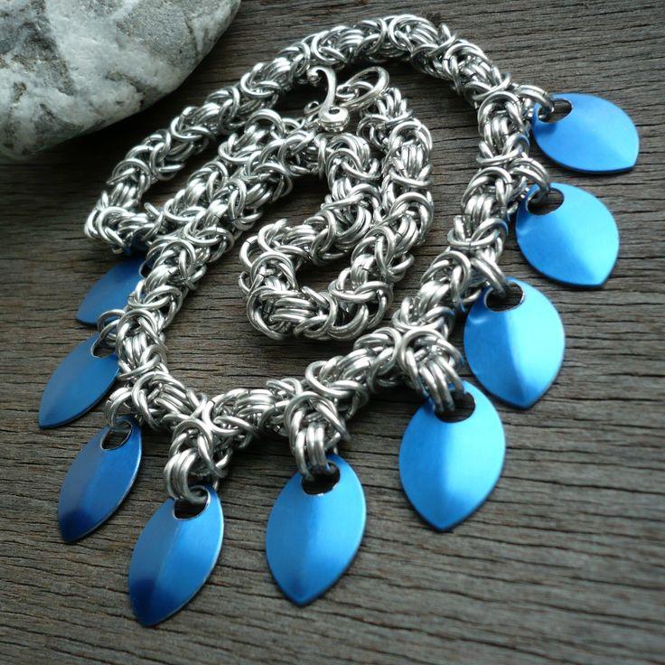 Byzantine se šupinami Výrazný náhrdelník z eloxovaných hliníkových kroužků a modrých hliníkových šupin. Použita byzantská vazba. Délka náhrdelníku 46 cm, starostříbrné zapínání ve tvaru slzy K náhrdelníku se hodí náramek a náušnice s šupinami