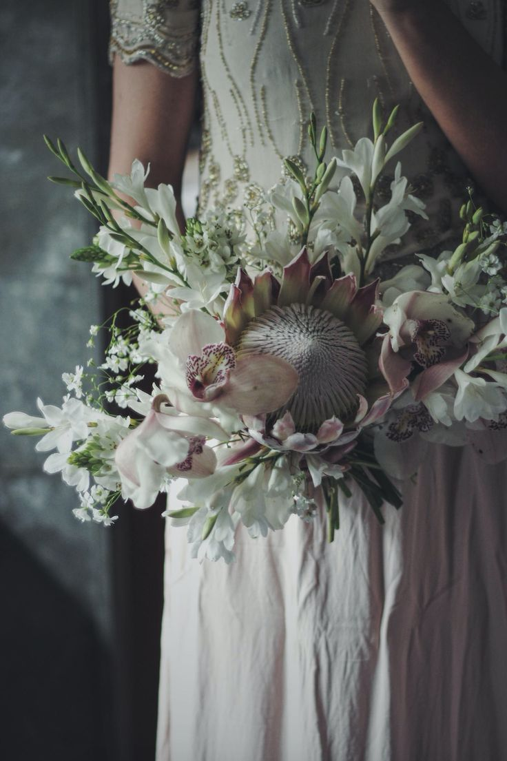 Flowers by Kent Florist Jennifer Pinder. A homegrown blush pink rosequartz wedding bouquet with protea gladiolus orchids and ornithogalum. Perfect for a grey and dusky dusty pink themed wedding.