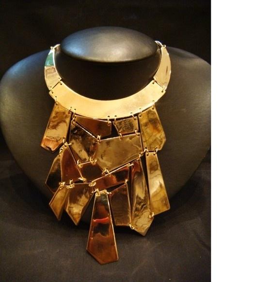 Maxi colar em metal banho dourado. Cortes assimétricos formando uma ousada franja de placas ligadas por delicados argolas.