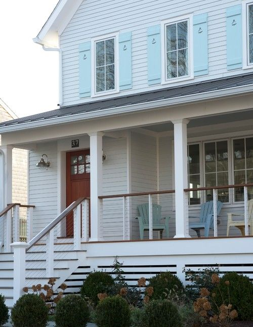 Farmhouse Porch with Colorful Adirondack Chairs