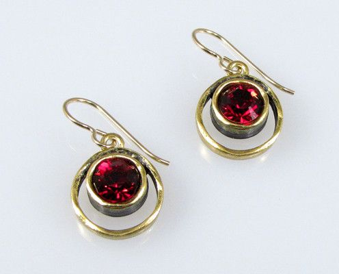 Patricia Locke Jewelry - Skeeball Earrings in Ruby Shown here is Patricia Locke's Skeeball Earrings rendered in Antique Gold and accented with Ruby colored Austrian Crystals. Measuring approximately .