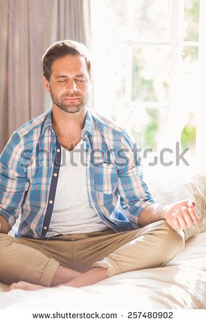 Handsome man doing yoga on his bed at home in bedroom