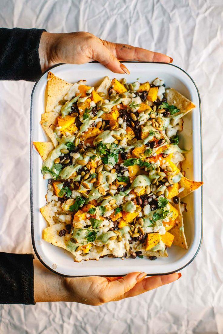"Loaded Vegetarian Pumpkin Nachos with black beans, roasted pumpkin, queso fresco, cilantro lime cream sauce, cilantro, pepitas, and greek yogurt. It's a healthy and seasonal way to eat ""junk food!"" #recipe #vegetarian #nachos   Brewing Happiness"