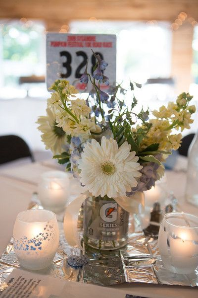 We had Gatorade bottles for vases of our centerpieces and we copied race bibs from our races together to use as table numbers. I also used squares of space blankets under the centerpieces. #running #wedding #runningwedding