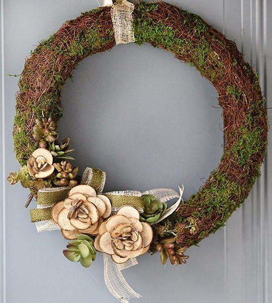 eenvoudige deurkrans, natuurlijke materialen, mos en houten bloemen, kan je zelf maken, en niet duur.