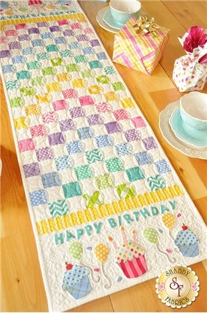 Patchwork Birthday Table Runner Pattern: Celebrate a birthday with this colorful table runner! Patchwork makes up the center of this runner and each end features fusible applique cupcakes, balloons and the words Happy Birthday!